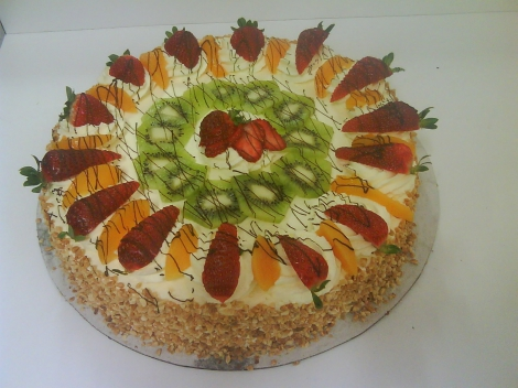 Pavlova topped with seasonal fruit and fresh cream.