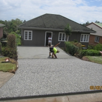 Exposed chequerboard mix Driveway and plain concrete Carport with a machine finish.