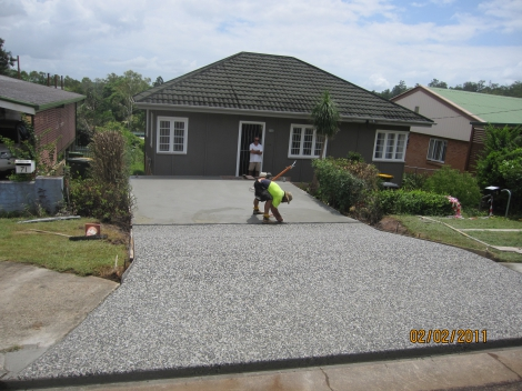 Exposed brown & white mix Driveway and plain concrete Carport with a machine finish.