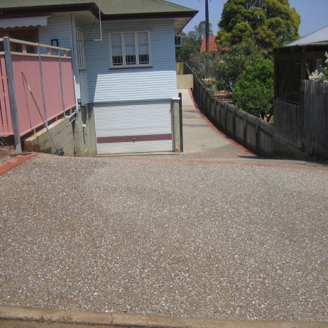 Exposed clarence mix Driveway with Paving Edges/Control Joints & built front timber Fenceline.