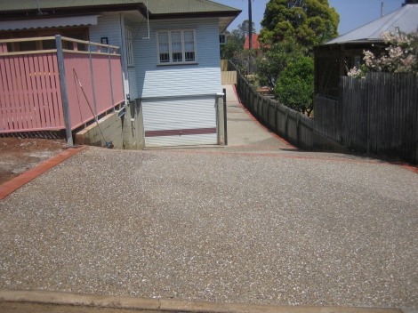 Exposed brown & white mix Path, Driveway with Paving Edges & built front timber Fenceline.