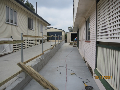 2 x plain concrete Driveways with block Retaining Wall & timber Fencline inbetween with steel posts.