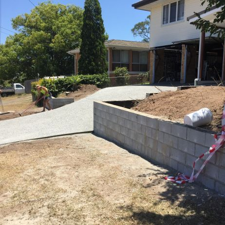 AFTER PHOTO:  Constructed new eclipse exposed driveway with besser block retaining front fenceline.