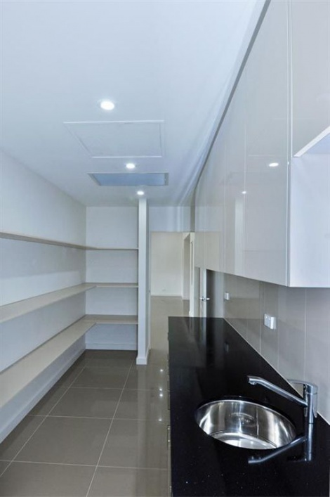 WALL OF SHELVING IN A BUTLERS PANTRY