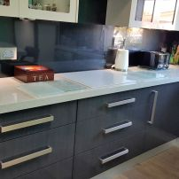 BANK OF DRAWERS, VERY LARGE MODERN HANDLES, 50MM BENCH TOP AND A WHITE INDUCTION COOKTOP.