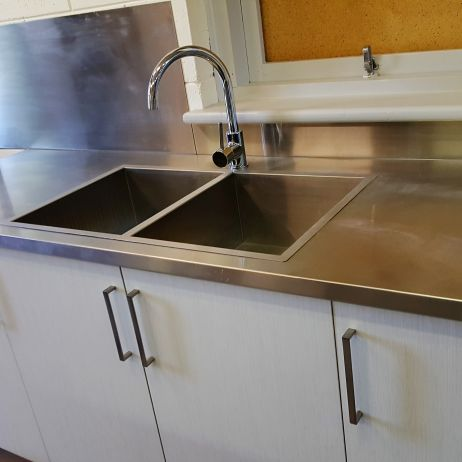 SALVATION ARMY COMMERCIAL KITCHEN . THE FLAT EDGED SINKS BLEND  WELL WITH THE STAINLESS STEEL BENCH